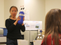Wei Wang shows an air bottle to students before they conduct an atmospheric experiment. Photo by Shelly Sommer, April 2014.